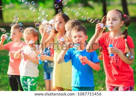 Group of children blowing soap bubbles #1087715456