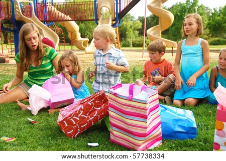 Group of children celebrate girl's birthday at a park - stock photo
