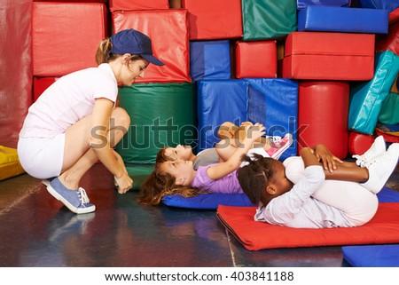Group of children doing gymnastics in preschool with PE teacher