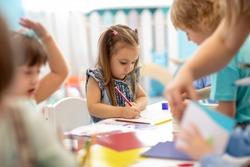 Group of children drawing with nursery teacher in kindergarten
