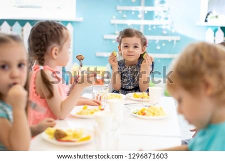 Group of children eating healthy food in kindergarten Photo stock ©