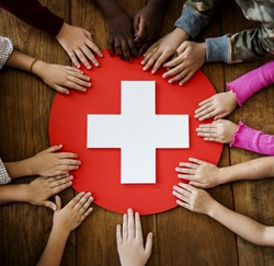 Group of children hands holding red cross symbol