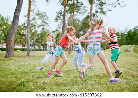 Group of children holding hands and dancing in circle on green lawn in park on beautiful summer day