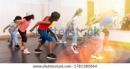 Group of children in casual clothes training hip-hop in class, learning modern dance movements Stock fotó ©