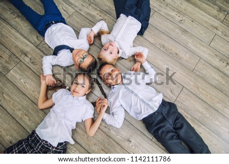 Group of children in school uniform cheerful and beautiful smile lying on the floor