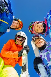 Group of children in ski in sport outfit mask ang helmets look down standing together over blue sky