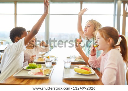 Group of children in the canteen having lunch or breakfast are having fun
