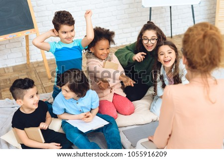 Group of children play a quiz with teacher in peach blouse while in primary school class. Children in elementary school are sitting in class.