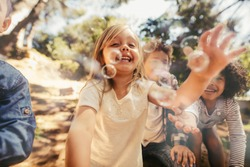 Group of children playing with soap bubbles in forest. Girl with friends catching the soap bubbles.