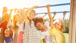 Group of children plays together at climbing frame on a playground in the summer