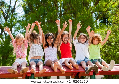 Group of children raising hands together in park.