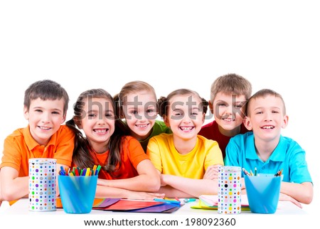 Group of children sitting at a table with markers, crayons and colored cardboard.