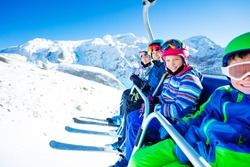 Group of children ski friends sit on chairlift lifting on the mountain top peak on sunny day