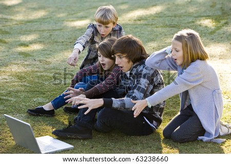 Group of children (10 to 15 years) shocked and fascinated by computer laptop