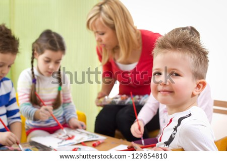 Group of children with aunt painting easter eggs