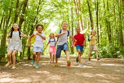 Group of children with backpack makes a race in nature in summer