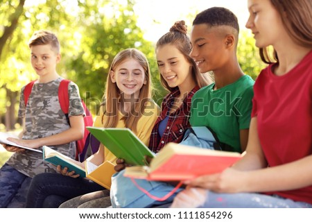 Group of children with books outdoors. Summer camp