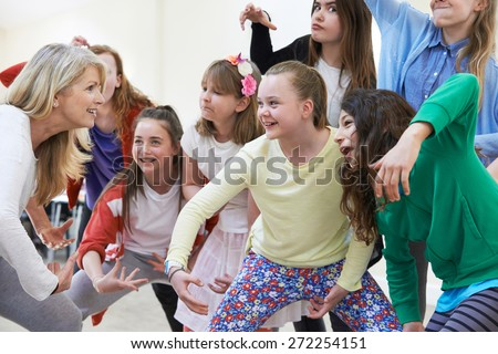 Photo of  Group Of Children With Teacher Enjoying Drama Class Together