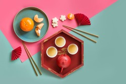 Group of Chinese New Year tea, red envelopes, tangerine and decorative items objects on light blue and pink background.