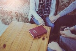 Group of Christian friends holding hands and prays together with the holy bible on the wooden table