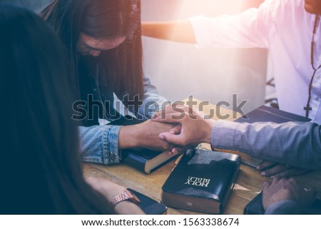 Group of Christians are congregants join hands to pray and seek the blessings of God, the Holy Bible. The cross symbol. They were reading the Bible and sharing the gospel with copy space. #1563338674