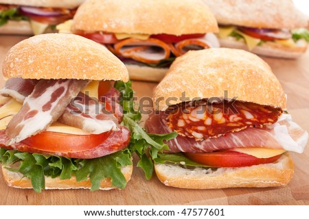 group of ciabatta bread sandwiches stuffed meat,cheese and vegetables