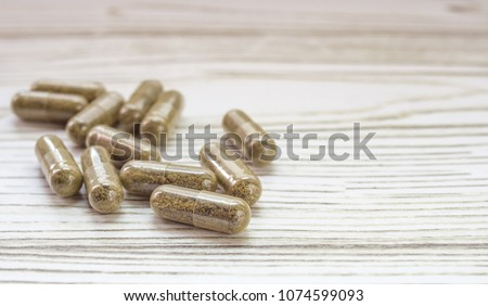 Group of clear CBD Cannabidiol capsules on bright wooden backdrop