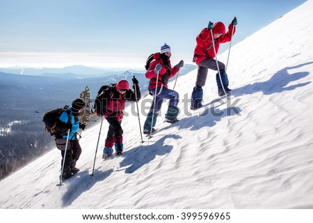 group of climbers climb the steep slopes of the snow-capped mountains on a clear day #399596965