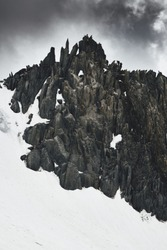 Group of climbers coming down from the summit of Mountain covered by snow and ice with dark rocks