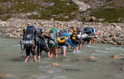 Group of climbers crossing the glacier river Electrico, on their way to the glacier Marconi, Los Glaciares National Park, Argentina.