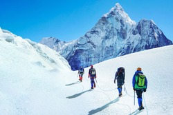 Group of climbers reaches the summit of mountain peak enjoying the landscape view in Nepal