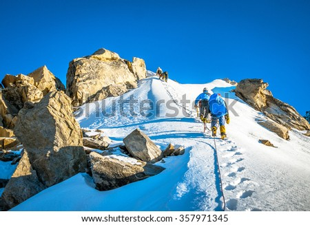 Group of climbers reaching the summit #357971345