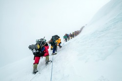 Group of climbers stuck on fixed ropes high on Manaslu (8163 m) in the Himalaya mountains