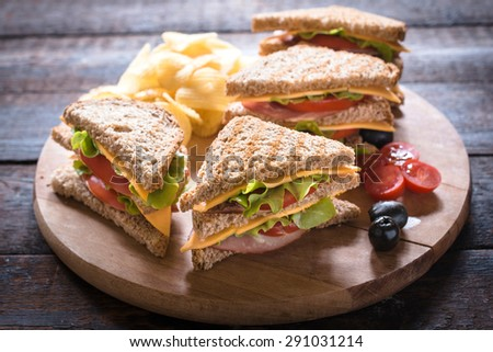 Group of club sandwiches with potato chips on wooden background,selective focus
