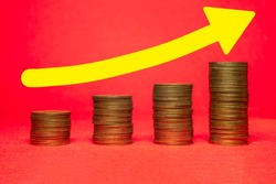 group of coin set in form of growth graph isolated on red background with yellow arrow pointing up. concept of investment growth.