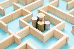 Group of coins heaps in the maze game built by wood blocks, find a way to money resource, business budget, making money concept