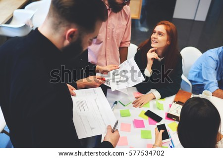 Group of colleagues going over paperwork together in a modern office. Positive way of discussing important questions. Team-workers analyzing together graphs and charts on printed statistic documents #577534702
