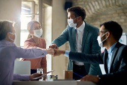Group of colleagues wearing protective face masks and fist bumping while having business meeting during coronavirus pandemic.