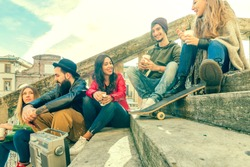 group of college friends gathering having fun chatting sitting on stairs outdoors. happy youngsters meeting outdoors. concept youth freedom togetherness joy and sharing. retro color tones