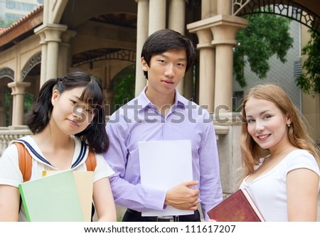 Group of college students holding books. American and Asian teenagers studying outside of university campus