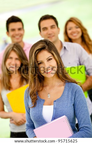 Group of college students holding notebooks and smiling
