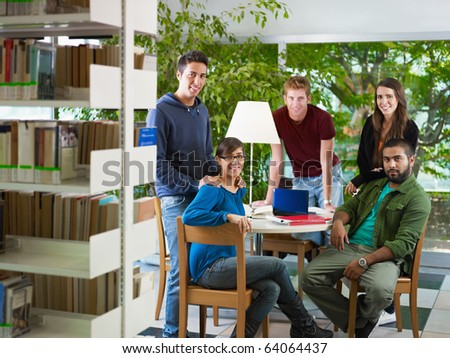 group of college students looking at camera in library. Horizontal shape, front view, full length