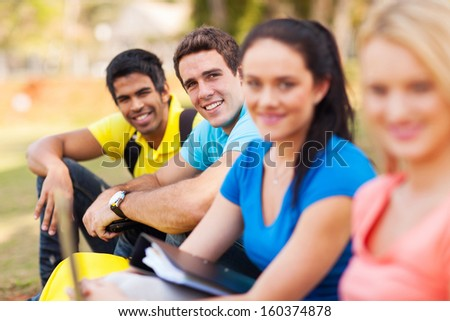 group of college students sitting outdoors on campus - stock photo