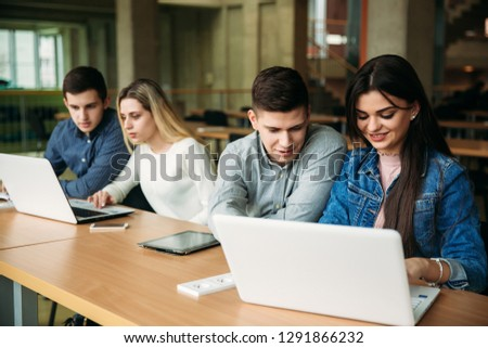 Group of college students studying in the school library, a girl and a boy are using a laptop and connecting to internet. Prepare for an exam