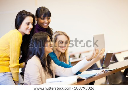 group of college students using tablet computer in classroom