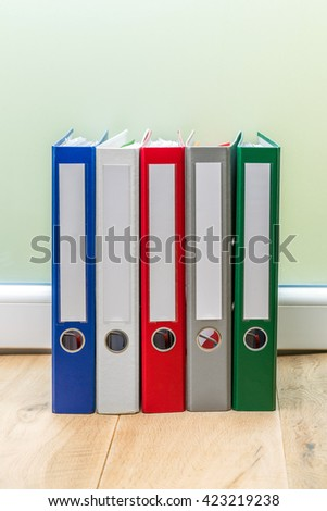 Group of colourful folders in a row on wooden table