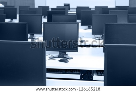Group of computer neatly placed in a computer lab.