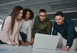 Group of concentrated diverse business team discussing information on laptop screen over the desk in office