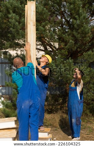 Group of construction workers aligning a prefab wooden wall panel on a new build house