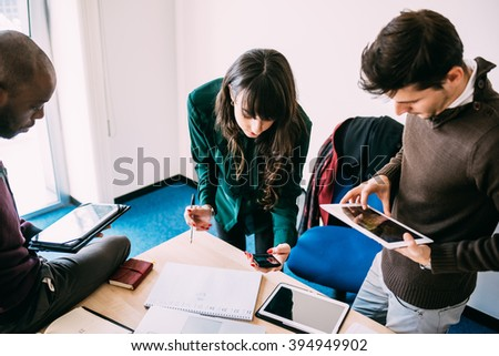 Group of contemporary multiethnic business people working together using multimedia devices like smart phone and tablet - working, business, start up concept #394949902